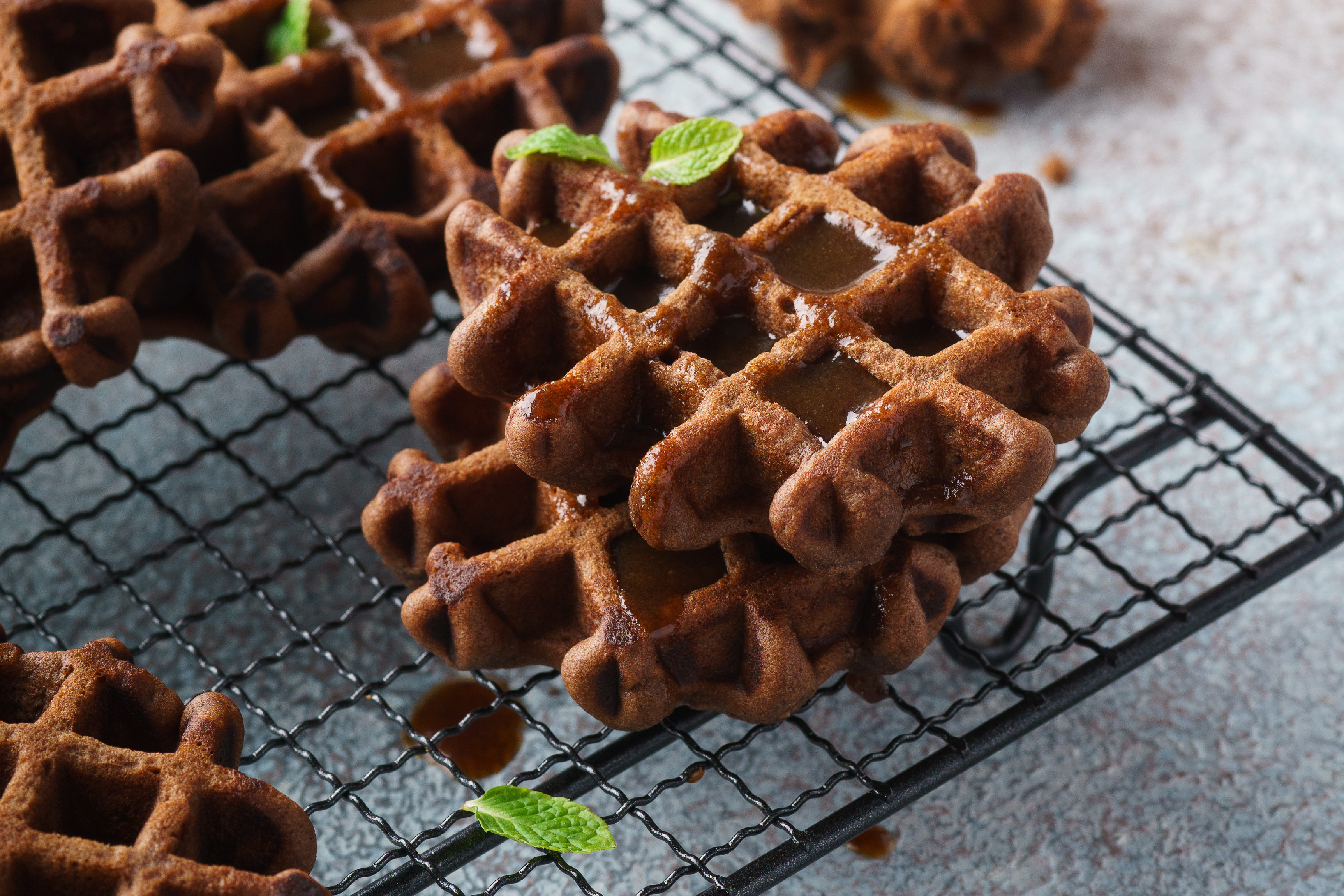 Chocolate waffles with caramel syrup and mint for breakfast.